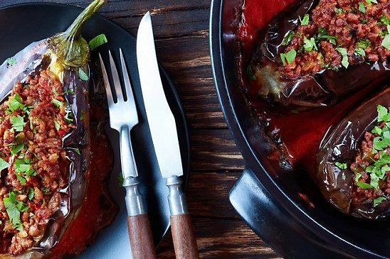 Stuffed Aubergine on a black plate and a knife and fork with wooden handles on a dark wooden table.